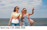 Купить «teenage girls or friends walking at seaside», видеоролик № 31090705, снято 25 июня 2019 г. (c) Syda Productions / Фотобанк Лори