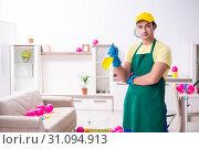 Купить «Young male contractor doing housework after party», фото № 31094913, снято 14 марта 2019 г. (c) Elnur / Фотобанк Лори