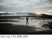 Купить «A person walking over a black sand beach at sunset in Stokksnes, Iceland.», фото № 31098393, снято 1 января 2018 г. (c) easy Fotostock / Фотобанк Лори