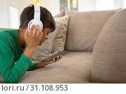Купить «Boy with headset listening music on mobile phone on sofa in a comfortable home», фото № 31108953, снято 19 марта 2019 г. (c) Wavebreak Media / Фотобанк Лори