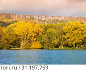 Sandstone rock formation in the middle of colorful autumn forest. Water surface on the foreground. Dramatic evening view. Tisa Rocks, aka Tiske Walls, Czech-Saxon Switzerland, Czech Republic. Стоковое фото, фотограф YAY Micro / easy Fotostock / Фотобанк Лори