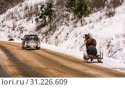 Купить «Volovets, Ukraine - December 16, 2016: traffic in mountainous rural area in winter. cart with one horse outscored by SUV on snowy countryside road», фото № 31226609, снято 16 декабря 2016 г. (c) easy Fotostock / Фотобанк Лори