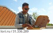 Купить «indian man eating pizza and drinking beer outdoors», видеоролик № 31336289, снято 30 июня 2019 г. (c) Syda Productions / Фотобанк Лори
