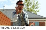 Купить «man with smartphone and headphones on roof top», видеоролик № 31336329, снято 30 июня 2019 г. (c) Syda Productions / Фотобанк Лори