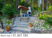 Купить «A composition on historical themes located on the edge of the forest on the site with the steps leading to it. There is a flowerpot with flowers hanging under the wooden roof.», фото № 31367185, снято 15 июля 2014 г. (c) easy Fotostock / Фотобанк Лори