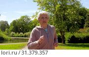 Купить «senior woman with earphones running in summer park», видеоролик № 31379357, снято 1 июля 2019 г. (c) Syda Productions / Фотобанк Лори
