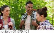 Купить «friends with backpacks on hike talking in forest», видеоролик № 31379401, снято 29 июня 2019 г. (c) Syda Productions / Фотобанк Лори
