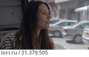 Купить «A longhaired girl sitting in a bus and looking outside the window», видеоролик № 31379505, снято 16 июля 2019 г. (c) Данил Руденко / Фотобанк Лори