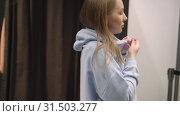 Купить «Pretty young woman trying on blue sweatshirt, puts a hood over her head», видеоролик № 31503277, снято 2 июля 2019 г. (c) Ирина Мойсеева / Фотобанк Лори