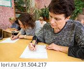 Купить «Взрослые люди за школьными партами проходят тестирование по русскому языку», фото № 31504217, снято 13 апреля 2019 г. (c) Вячеслав Палес / Фотобанк Лори