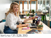 Купить «Female graphic designer holding a color swatch while using laptop at desk in office», фото № 31526393, снято 17 марта 2019 г. (c) Wavebreak Media / Фотобанк Лори