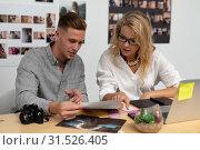 Купить «Male and female graphic designers discussing over photo at desk», фото № 31526405, снято 17 марта 2019 г. (c) Wavebreak Media / Фотобанк Лори