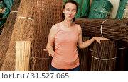 Купить «Woman chooses decorative fence from twigs in store», видеоролик № 31527065, снято 26 мая 2019 г. (c) Яков Филимонов / Фотобанк Лори
