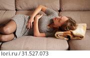 Купить «Unhappy woman having stomachache lying on couch at home», видеоролик № 31527073, снято 12 марта 2019 г. (c) Яков Филимонов / Фотобанк Лори