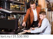 Купить «Laughing boy and father deciding on synthesizer», фото № 31530993, снято 29 марта 2017 г. (c) Яков Филимонов / Фотобанк Лори