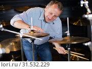 Купить «Man is choosing drum set», фото № 31532229, снято 18 сентября 2017 г. (c) Яков Филимонов / Фотобанк Лори