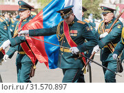 Купить «Officer of the banner group, sheathes his saber. Orenburg, Russia - May 9, 2019: Victory Parade on Lenin Square», фото № 31570897, снято 9 мая 2019 г. (c) Вадим Орлов / Фотобанк Лори