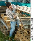 Купить «Man repairs wooden pallets in the backyard of a country house», фото № 31596281, снято 28 февраля 2019 г. (c) Яков Филимонов / Фотобанк Лори