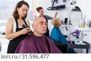 Купить «Hairdresser doing styling of man», фото № 31596477, снято 26 июня 2018 г. (c) Яков Филимонов / Фотобанк Лори