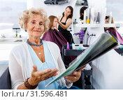 Smiling elderly female client sitting with magazine in chair in hair salon, choosing new hairstyle. Стоковое фото, фотограф Яков Филимонов / Фотобанк Лори