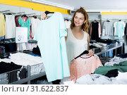 Купить «Brunette choosing new clothes in shop», фото № 31622837, снято 19 июня 2017 г. (c) Яков Филимонов / Фотобанк Лори