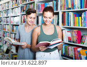 portrait of teenage boy and girl customers looking at open book standing among bookshelves. Стоковое фото, фотограф Яков Филимонов / Фотобанк Лори