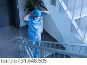 Купить «Male surgeon wearing surgical mask while going down the stairs of hospital», фото № 31648605, снято 9 марта 2019 г. (c) Wavebreak Media / Фотобанк Лори