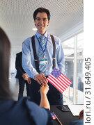 Купить «Businessman holding an American flag at conference registration table», фото № 31649405, снято 16 марта 2019 г. (c) Wavebreak Media / Фотобанк Лори