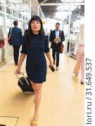 Купить «Businesswoman walking with luggage in corridor at office», фото № 31649537, снято 16 марта 2019 г. (c) Wavebreak Media / Фотобанк Лори