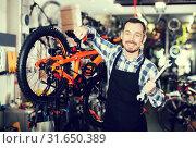 Купить «Man working on master mechanic assembling bicycle equipment», фото № 31650389, снято 22 августа 2019 г. (c) Яков Филимонов / Фотобанк Лори