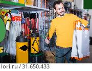 Купить «Guy selects a garden sprayer», фото № 31650433, снято 2 марта 2017 г. (c) Яков Филимонов / Фотобанк Лори