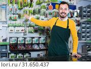 Купить «benevolent male seller showing assortment in garden equipment shop», фото № 31650437, снято 2 марта 2017 г. (c) Яков Филимонов / Фотобанк Лори