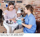 Купить «Woman client choosing color of nail polish», фото № 31650597, снято 30 мая 2018 г. (c) Яков Филимонов / Фотобанк Лори