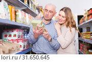 Couple customers looking groats in grocery food shop. Стоковое фото, фотограф Яков Филимонов / Фотобанк Лори