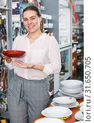 Купить «Young woman consumer ceramic plates in tableware shop», фото № 31650705, снято 2 мая 2018 г. (c) Яков Филимонов / Фотобанк Лори