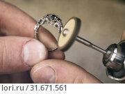 Ювелир полирует золотое кольцо в мастерской, рабочий процесс. Стоковое фото, фотограф Сергей Чайко / Фотобанк Лори