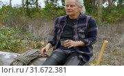 Купить «Lumberjack relaxing on fallen tree 4k», видеоролик № 31672381, снято 13 августа 2018 г. (c) Wavebreak Media / Фотобанк Лори
