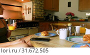 Купить «Woman having food on dining table in kitchen 4k», видеоролик № 31672505, снято 11 июля 2018 г. (c) Wavebreak Media / Фотобанк Лори