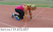 Купить «Side view of young Caucasian female athlete taking starting position on running track 4k», видеоролик № 31672657, снято 17 апреля 2018 г. (c) Wavebreak Media / Фотобанк Лори