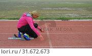 Купить «Side view of Caucasian female athlete taking starting position on running track at sports venue 4k», видеоролик № 31672673, снято 17 апреля 2018 г. (c) Wavebreak Media / Фотобанк Лори