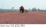 Купить «Front view of Caucasian female athlete taking starting position on running track at sports venue 4k», видеоролик № 31672781, снято 17 апреля 2018 г. (c) Wavebreak Media / Фотобанк Лори
