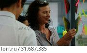 Купить «Executive working on sticky note on glass wall 4k», видеоролик № 31687385, снято 1 сентября 2018 г. (c) Wavebreak Media / Фотобанк Лори