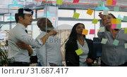 Купить «Executives discussing over sticky note on glass wall 4k», видеоролик № 31687417, снято 1 сентября 2018 г. (c) Wavebreak Media / Фотобанк Лори