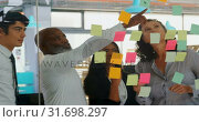 Купить «Executives discussing over sticky note on glass wall 4k», видеоролик № 31698297, снято 1 сентября 2018 г. (c) Wavebreak Media / Фотобанк Лори