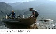 Купить «Two fishermen preparing for fishing in the river 4k», видеоролик № 31698329, снято 30 июля 2018 г. (c) Wavebreak Media / Фотобанк Лори