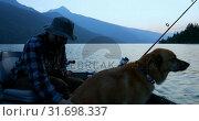 Купить «Fisherman fishing with his dog in the river 4k», видеоролик № 31698337, снято 30 июля 2018 г. (c) Wavebreak Media / Фотобанк Лори