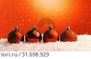 Купить « Christmas animation of glittery orange Christmas baubles placed in a row in snow 4k», видеоролик № 31698929, снято 26 октября 2018 г. (c) Wavebreak Media / Фотобанк Лори