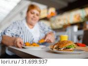 Fat woman eating nuggets in mall food court. Стоковое фото, фотограф Tryapitsyn Sergiy / Фотобанк Лори