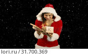 Купить «Video composition with falling snow over happy girl in santas suit opening gift box», видеоролик № 31700369, снято 2 ноября 2018 г. (c) Wavebreak Media / Фотобанк Лори
