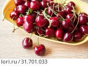 Купить «Ripe juicy red berries of a sweet cherry in a dish on a wooden table. Top view close-up», фото № 31701033, снято 25 июня 2019 г. (c) Юлия Бабкина / Фотобанк Лори